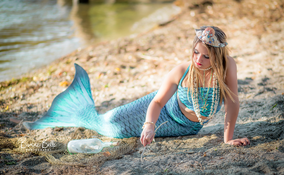 MERMAID DRAWS IN SAND WITH STICK IN OKANAGAN